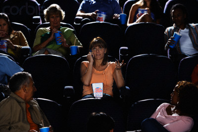 Woman Using Cell Phone During Movie